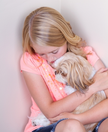 Sad teen in corner holding her shih tzu dog for comfort photo
