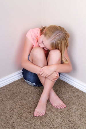 little girl: Sad teen sitting in corner with sad look on her face