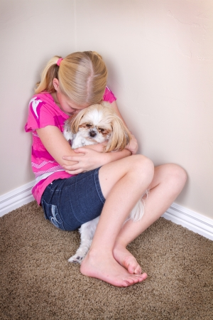 sad child in corner hugging her dog for comfort