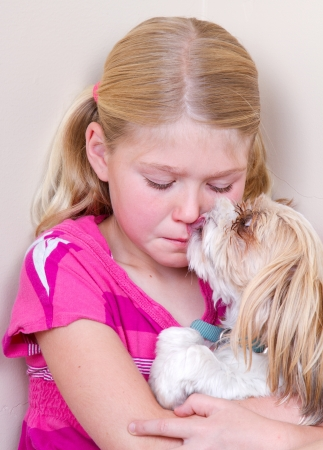 sad child sitting in corner with dog licking her face trying to comfort her.