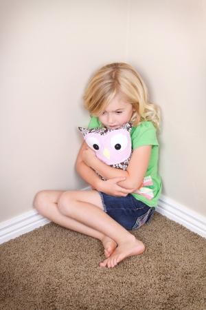 幼児または幼児の顔に悲しげな表情で、隅に座っている快適さのための動物のぬいぐるみを保持