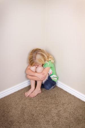 mirada triste: Ni�o joven o ni�o en edad preescolar se sienta en esquina, con una mirada triste en el rostro Foto de archivo
