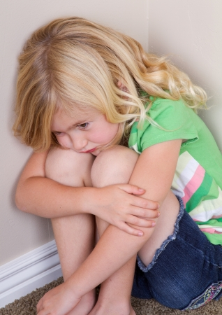 fear of failure: Young child or preschooler sitting in corner, with a sad look on face Stock Photo