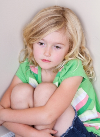 domestic: Young child or preschooler sitting in corner, with a sad look on face Stock Photo