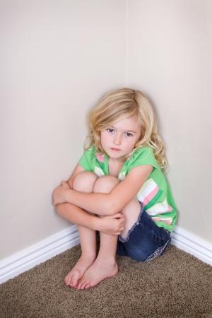 Jong kind of kleuter zit in de hoek, met een droevige blik op gezicht Stockfoto