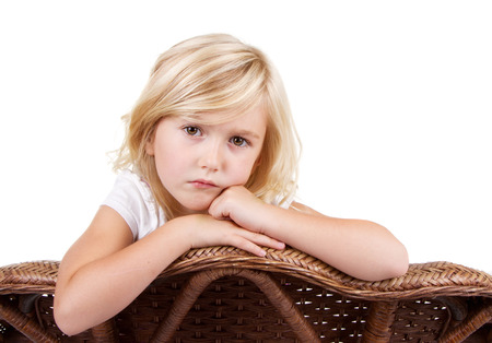 punished: Little girl sitting in chair with a sad or lonely look on her face, isolated on white background.