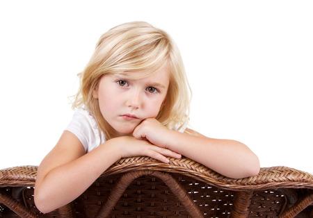 petite fille triste: Petite fille assise dans un fauteuil avec un regard triste ou solitaire sur son visage, isolé sur fond blanc. Banque d'images
