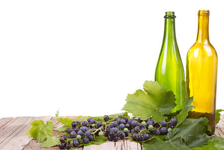 grapes on vine with leaves with empty wine bottles sitting on wooden plank with an isolated white background photo