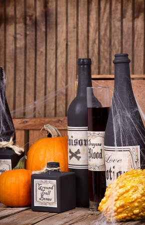 Potion bottles with pumpkins and gourds on wooden planks photo