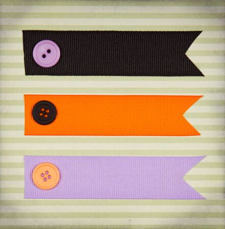 Halloween colored ribbon tags with sewing buttons on paper background for copy space photo