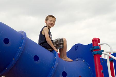 niño escalando: Niño que sube en juegos infantiles exterior Foto de archivo