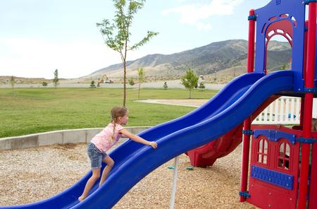 niño trepando: Niño que sube hasta la diapositiva en equiptment patio exterior