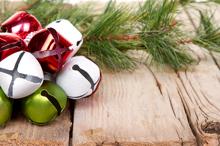 Christmas Jingle bells and a pine branch on a rustic wooden plank