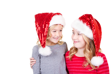 Sisters or two young girls wearing Santa hats looking at each other on an isolated white background photo