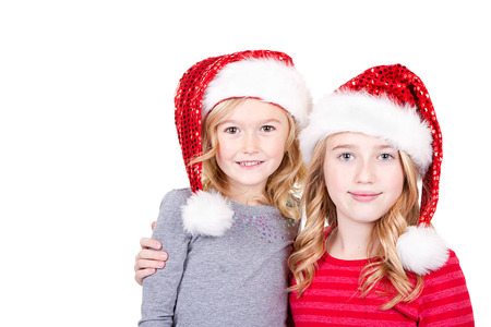Sisters or two young girls wearing Santa hats  on an isolated white background photo