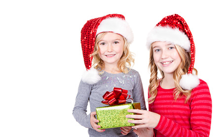 Sisters or two young girls wearing Santa hats holding a present on an isolated white background photo