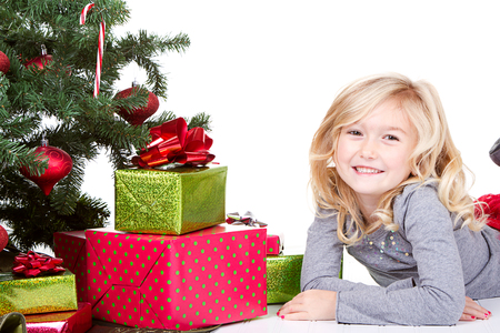 Child next to a Christmas tree with presents with and isolated white background