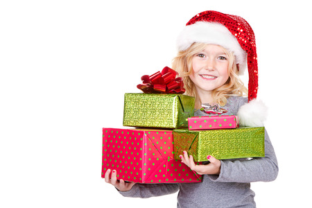 Young child holding large stack of Christmas presents wearing a Santa hat isolated on white photo
