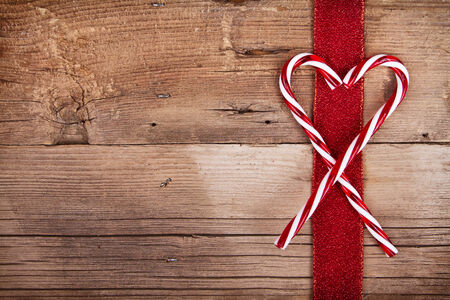 Candy canes and ribbon on rustic wooden background Foto de archivo
