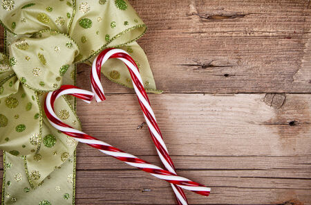 Christmas ribbon with candy canes on a rustic wooden background Imagens