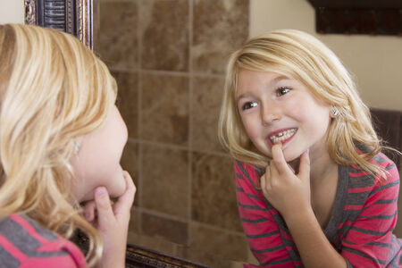 tooth fairy: Child looking in mirror and pointing at missing front tooth