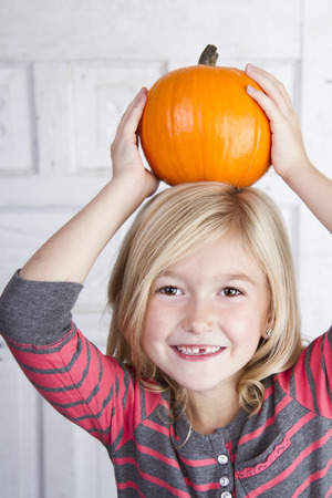 Cute child holding small pumpkin on her head