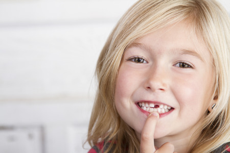 Child missing front tooth pointing at it with her finger Imagens