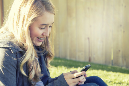 Teenage girl smiling while using a cell phone, texting, surfing the internet or playing a game, in an outdoor setting.
