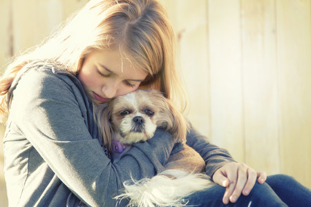 A sad or depressed teenage girl hugging a small dog in an outdoor setting
