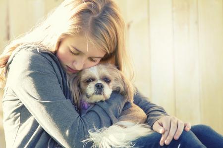niños tristes: Una adolescente triste o deprimido que abraza un pequeño perro en un escenario al aire libre