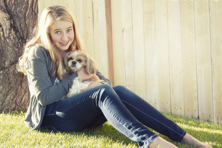 Teenage girl holding a small dog in an outdoor setting photo