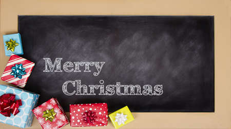Christmas presents grouped around a chalkboard with Merry Christmas written on it. photo