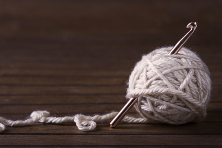 Ball of cream yarn with crochet hook or needle sticking through Stockfoto