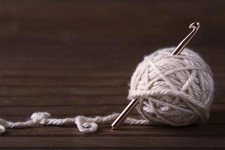gomitoli di lana: Sfera di filato crema con uncinetto o un ago attaccare attraverso Archivio Fotografico