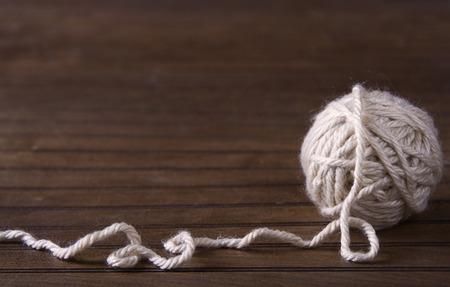 unwinding: Ball of cream yarn unwinding onto a brown wooden background