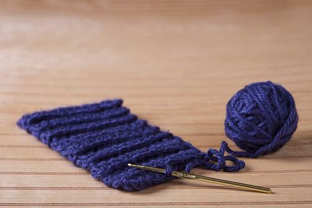 knitting needles: Ball of blue yarn with crochet needle making scarf