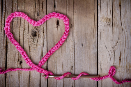 A crochet chain in the shape of a heart on a rustic wooden background