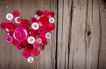 Sewing buttons in the shape of a heart on a rustic wooden background photo