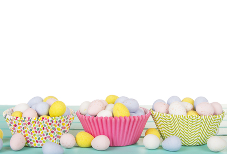 candy background: Easter Candy in cup cake wrappers on a turquoise blue wood panel