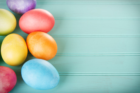colored dye: Dyed Easter eggs on a turquoise blue wooden panel