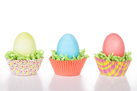 hard boiled: Dyed Easter eggs in a nest of green grass confetti and cup cake wrappers Stock Photo