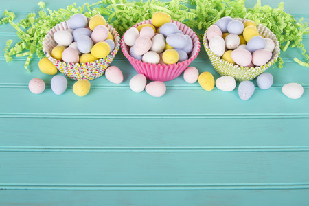 Easter Candy in colorful cupcake wrappers with green confetti on a turquoise blue wooden panel