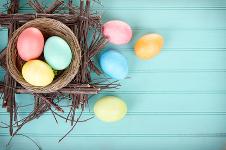 dipped: Dyed Easter eggs in a nest on a turquoise blue wood panel