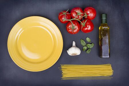 A collection of ingredients for spaghetti including pasta, tomatoes, garlic, basil and olive oil on a chalkboard background photo