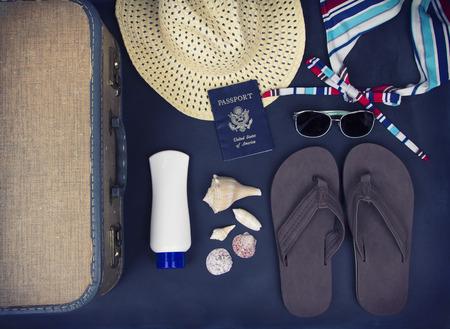 foto carnet: Una colección de artículos de viaje incluyendo maleta, pasaporte, sandalias, gafas de sol, traje de baño, protector solar y sombrero de paja en el fondo pizarra Foto de archivo