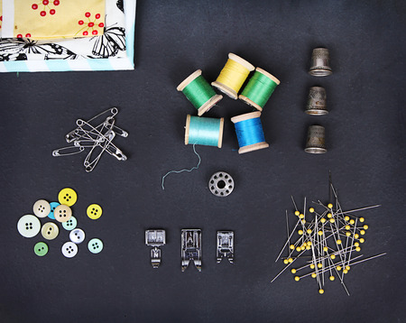 A collection of sewing items including: thread, thimbles, pins, buttons, bobbin, sewing machine feet and material on a chalkboard background photo