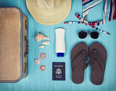 birds eye view: A collection of travel items including suitcase, passport, sandals, sunglasses, swim suit, sunscreen and straw hat on turquoise background