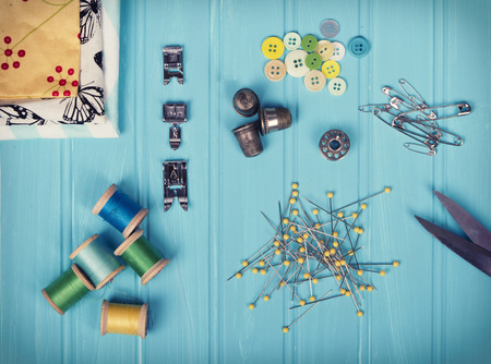 bobbin: A collection of sewing items including: thread, thimbles, pins, buttons, bobbin, sewing machine feet and material on a turquoise background