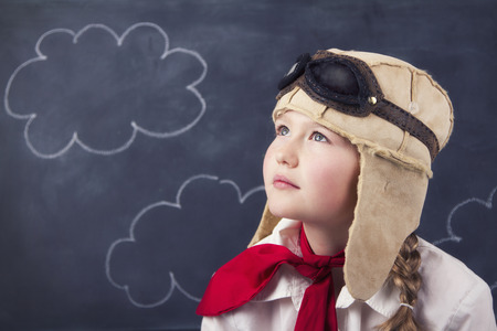 Young girl with aviator goggles and hat with calk board and clouds in background