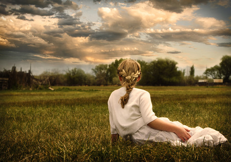 timeless: Young girl wearing a white dress sitting in a grassy pasture or prairie looking at sunset